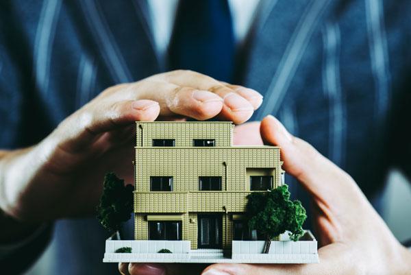 住宅模型を持つビジネスマンの手