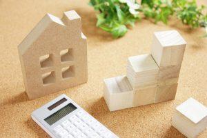 土地を持っている人の新築アパートの利回りの目安 電卓と積み木と住宅模型
